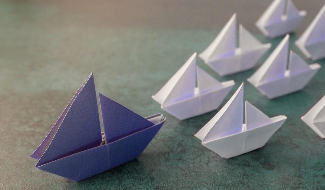 Egy színes paírhajót követ sok fehér papírhajó